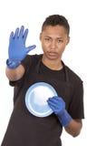 Hombre joven hispánico que lleva guantes azules de la limpieza Foto de archivo libre de regalías