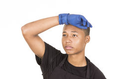 Hombre joven hispánico que lleva los guantes azules de la limpieza que hacen frente a la cámara con el brazo derecho aumentado Imágenes de archivo libres de regalías