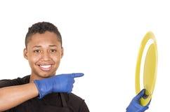 Hombre joven hispánico que lleva los guantes azules de la limpieza que soportan la placa amarilla y que sonríen a la cámara Imagenes de archivo