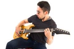 Hombre joven hispánico que toca la guitarra eléctrica Imagen de archivo