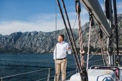 Hombre joven impresionante en el yate de lujo que navega abajo del mar en weddin Imágenes de archivo libres de regalías