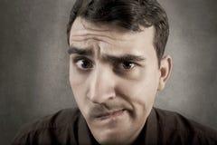 Hombre joven indeciso del estudiante aislado sobre fondo gris foto de archivo libre de regalías