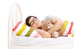 Hombre joven infantil que duerme con un oso de peluche Fotografía de archivo libre de regalías