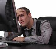 Hombre joven infeliz delante del ordenador fotos de archivo