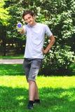 Hombre joven interactivo que comunica por un smartphone en un parque Imagenes de archivo