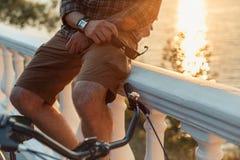 Hombre joven irreconocible con restos de las bicicletas en el concepto de piedra de Summer Vacation Travel de la cerca imagenes de archivo