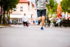 Hombre joven irreconocible que corre en la ciudad, calle principal Imagen de archivo
