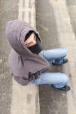 Hombre joven irreconocible que lleva el pasamontañas negro que se sienta en viejo Fotos de archivo libres de regalías