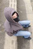 Hombre joven irreconocible que lleva el pasamontañas negro que se sienta en viejo Imagenes de archivo