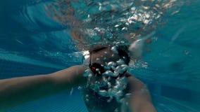 Hombre joven juguetón en vidrios anaranjados en la piscina Tiempo de verano de las vacaciones Cámara de la acción almacen de metraje de vídeo