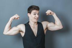 Hombre joven juguetón que dobla los músculos que muestran el poder masculino imagenes de archivo