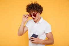 Hombre joven juguetón que guiña y que mira sobre las lentes Imagenes de archivo