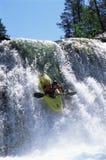 Hombre joven kayaking abajo de la cascada Imagenes de archivo