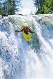 Hombre joven kayaking abajo de la cascada Foto de archivo libre de regalías