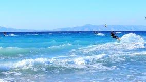 Hombre joven Kitesurfing en el océano que hace truco extremo metrajes