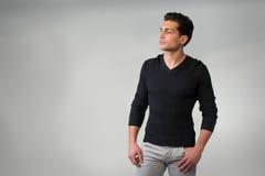 Hombre joven latino hermoso que se coloca en fondo gris. fotos de archivo libres de regalías