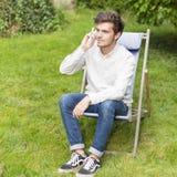 Hombre joven lindo con el teléfono que se sienta en el jardín Fotografía de archivo libre de regalías