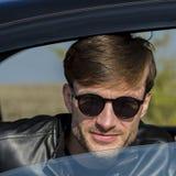 Hombre joven lindo en gafas de sol que sonríe y que mira fuera de un abierto Fotos de archivo