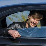 Hombre joven lindo que sonríe y que mira fuera de una ventanilla del coche abierta Imagen de archivo