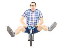 Hombre joven loco que presenta en una pequeña bicicleta Foto de archivo libre de regalías