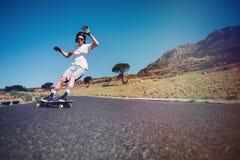 Hombre joven longboarding en un camino Imagen de archivo