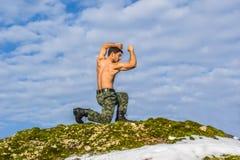 Hombre joven militar que entrena a artes marciales en naturaleza Imagen de archivo libre de regalías