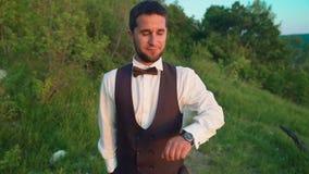 Hombre joven moderno al aire libre con el reloj elegante Alrededor de muchas plantas verdes almacen de video