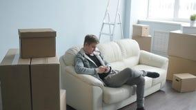 Hombre joven movido a un nuevo apartamento Se sienta en el sofá con un smartphone almacen de metraje de vídeo