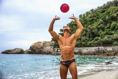Hombre joven muscular con el voleibol que juega voleo Imagen de archivo libre de regalías