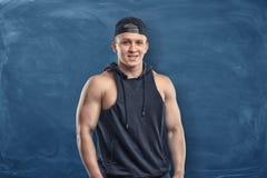 Hombre joven muscular en su ropa de deportes que se coloca y que sonríe en el fondo azul marino Fotos de archivo libres de regalías