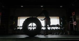 Hombre joven muscular fuerte que mueve de un tirón el neumático mientras que ejercita en el gimnasio de CrossFit El hombre se est almacen de video