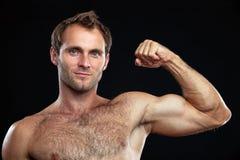 Hombre joven muscular que dobla su bicep Fotos de archivo