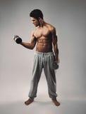 Hombre joven muscular que ejercita con pesas de gimnasia Imagenes de archivo