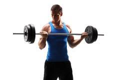 Hombre joven muscular que ejercita con un barbell Fotografía de archivo