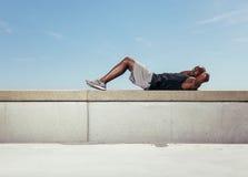 Hombre joven muscular que hace sentar-UPS Imagen de archivo libre de regalías