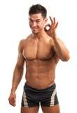 Hombre joven muscular que muestra la muestra aceptable Imagen de archivo libre de regalías