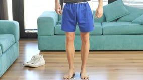 Hombre joven muscular que se pesa en escala, almacen de metraje de vídeo