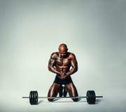 Hombre joven muscular que se resuelve con los pesos pesados Foto de archivo