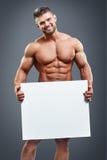 Hombre joven muscular que sostiene el cartel blanco en blanco Fotografía de archivo
