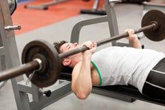 Hombre joven muscular que usa levantamiento de pesas Imágenes de archivo libres de regalías