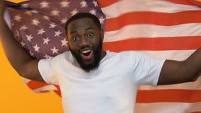 Hombre joven negro con la bandera americana que apoya el equipo nacional, entusiasmo del deporte almacen de metraje de vídeo