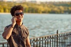 Hombre joven negro que habla en el teléfono móvil Fotografía de archivo libre de regalías