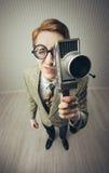 Hombre joven Nerdy con la cámara de película Fotos de archivo libres de regalías