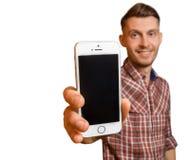 Hombre joven o adolescente atractivo que muestra su ` s del teléfono celular Imagen de archivo