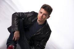 Hombre joven o adolescente hermoso que se sienta en el piso blanco Foto de archivo libre de regalías