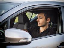 Hombre joven o adolescente serio que conduce el coche Imagenes de archivo