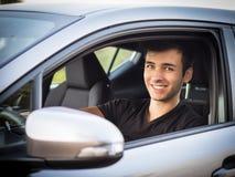 Hombre joven o adolescente serio que conduce el coche Foto de archivo libre de regalías