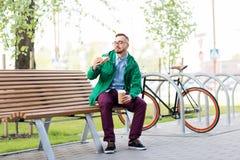 Hombre joven o inconformista con café que come el bocadillo imagen de archivo