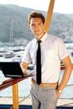 Hombre joven ocasional con la computadora portátil, colocándose Imágenes de archivo libres de regalías