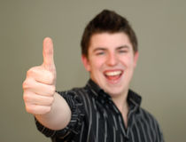Hombre joven ocasional que da los pulgares para arriba Imagenes de archivo
